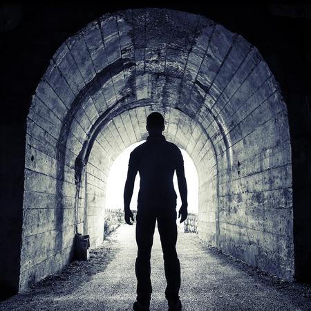 Jonge man staat in de donkere tunnel en kijkt in de gloeiende einde