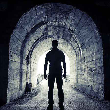 Young man stands in dark tunnel and looks in the glowing end
