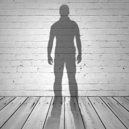Schaduw van een man op een witte bakstenen muur en houten vloer Stockfoto