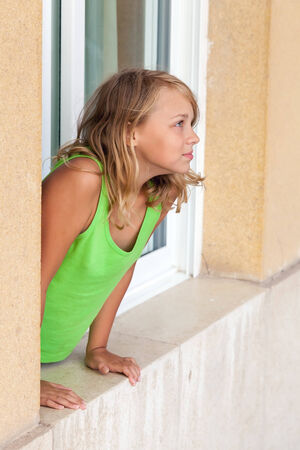 Little blond Caucasian girl in window, outdoor portrait photo