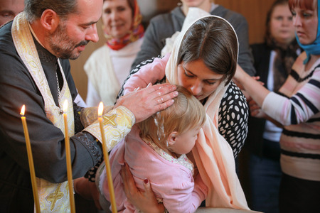 baptize: ST.PETERSBURG, RUSSIA - SEPTEMBER 21, 2014: Orthodox priest performs the rite of baptism for a little Russian girl in Our Lady of Vladimir Church in Saint-Petersburg