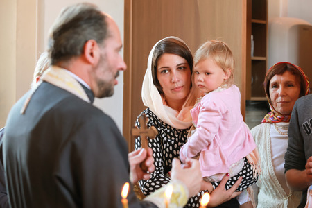 rite: ST.PETERSBURG, RUSSIA - SEPTEMBER 21, 2014: Orthodox priest performs the rite of baptism for a little Russian girl in Our Lady of Vladimir Church in Saint-Petersburg