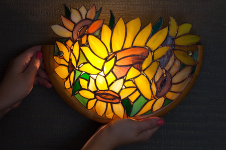 Handmade stained glass lamp with colorful sunflowers in womans hands photo