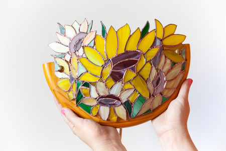 Handmade stained glass lamp with colorful sunflowers in womans hands on white background Stock Photo