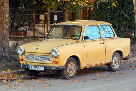 RUSE, BULGARIA - SEPTEMBER 29, 2014: Old yellow Trabant 601s car stands parked on a street side. It was the most common vehicle in East Germany with inefficient two-stroke engine