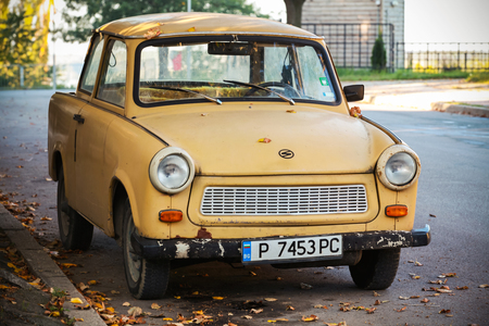 RUSE, BULGARIA - SEPTEMBER 29, 2014: Old yellow Trabant 601s car stands parked on a street side