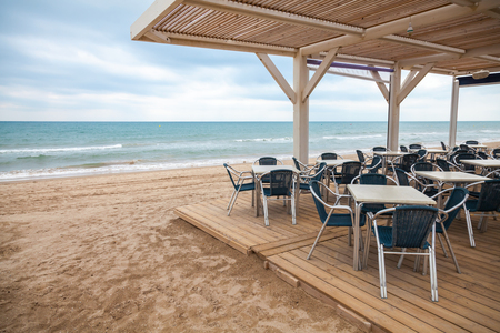 Sea side bar interior with wooden floor and metal armchairs on the sandy beach in Spain photo