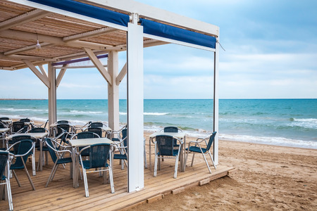 Sea side bar interior with wooden floor and metal armchairs on the sandy beach photo