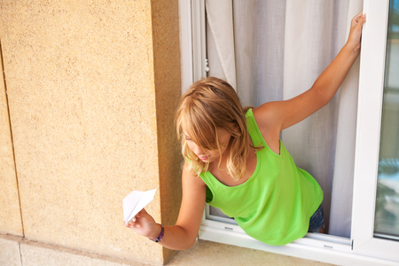 Little blond Caucasian girl with paper plane in the window photo