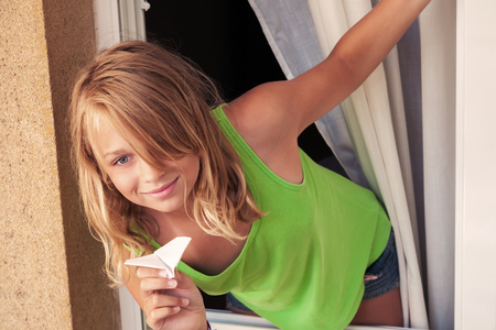 Little blond Caucasian girl with paper plane in the window, outdoor closeup portrait photo