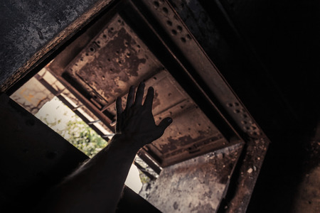 Grunge dark interior with open rusted door and male hand silhouette photo
