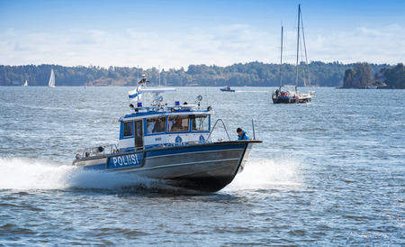 HELSINKI, FINLAND - SEPTEMBER 13, 2014: fast water police motor boat with policemen  sails in harbor of Helsinki
