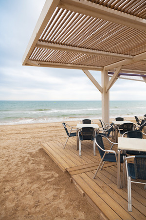 Sea side bar interior with wooden floor and metal armchairs on sandy beach in Spain photo