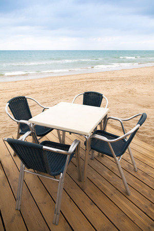 Open space sea side bar interior with wooden floor and metal armchairs on sandy beach photo