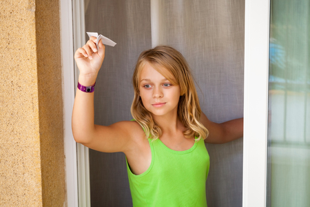 Little blond Caucasian girl with small paper plane in window, outdoor close-up portrait photo