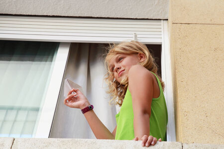 Little blond Caucasian girl with paper plane in window, outdoor close-up portrait photo