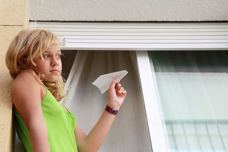 Little blond Caucasian girl with paper plane in window, outdoor closeup portrait photo