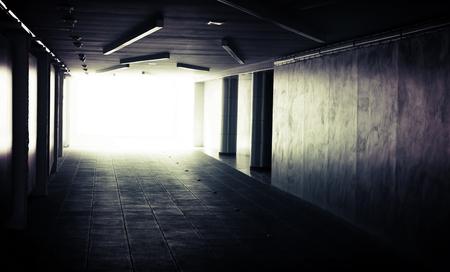 Abstract dark underground corridor interior with glowing end photo