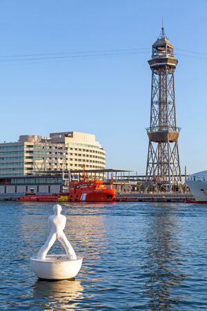 BARCELONA, SPAIN - AUGUST 27, 2014: vista port view with Montjuic cable car tower and white sculpture on the buoy