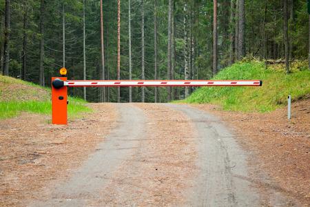 schlagbaum: Ländliche Straße im Wald mit geschlossenen rot-weiße Schranke Lizenzfreie Bilder