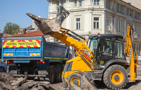 Ruse, Bulgaria - September 29, 2014: Road works. Highway maintenance, yellow tractor removes old asphalt pavement and loads in blue industrial truck