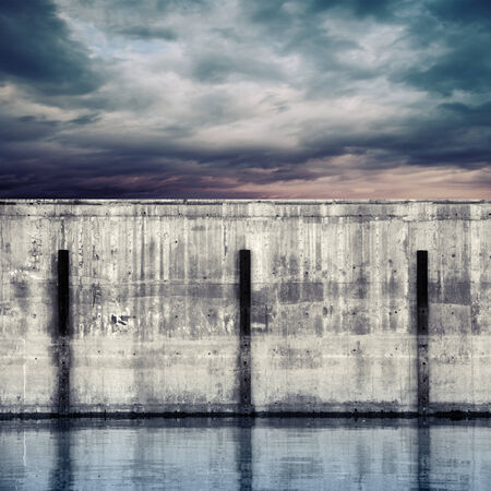 industry moody: Abstract port fragment. Gray concrete mooring wall with dark stormy sky