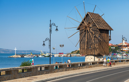 Nesebar, Bulgaria - July 21, 2014: Coastal landscape with old wooden windmill. Ancient town Nesebar, Bulgaria. Black Sea coast in sunny day