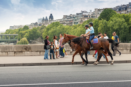 bystanders: Paris, France - August 07, 2014: Mounted police riding past the bystanders on the bridge in Paris