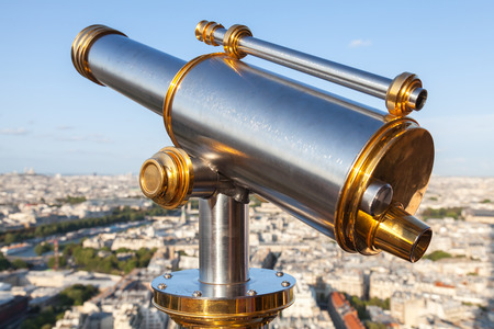 Shining metal telescope mounted on the railings of Eiffel Tower, Paris photo