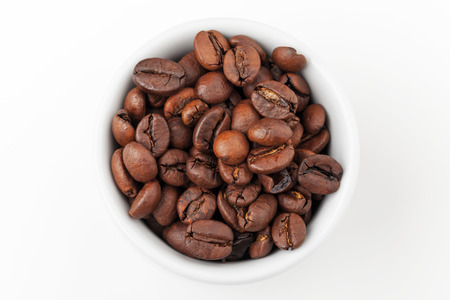 Small white espresso cup full of fresh roasted coffee beans on white background, top view photo