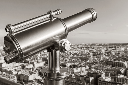 Shining metal telescope mounted on the railings of Eiffel Tower in Paris photo