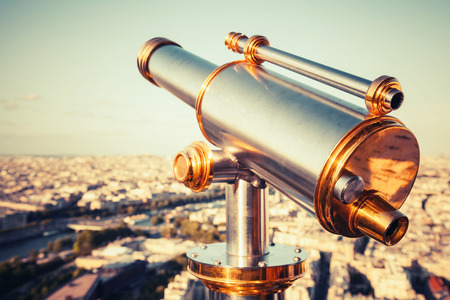Shining metal telescope mounted on the railings of Eiffel Tower, Paris.  photo