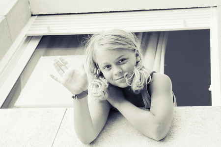 Young blond Caucasian girl showing hello gesture in the window, outdoor closeup monochrome portrait photo