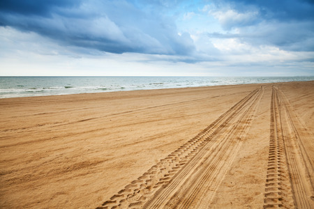 Perspective of tyre tracks on sandy beach with dark blue cloudy sky