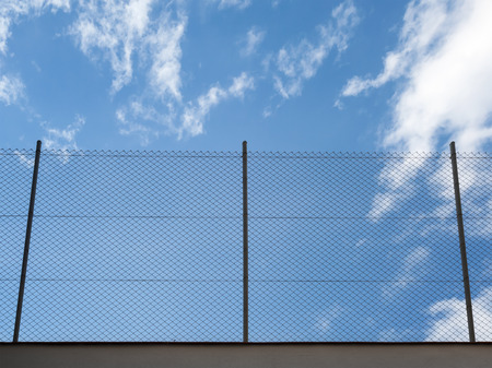 Metal Rabitz mesh fence against blue sky background photo