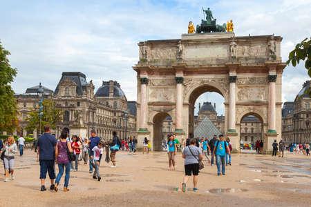 Paris, France - August 7, 2014: Tourists walk near The Triumphal Arch (de Triomphe du Carrousel) in front of  the Louvre museum, Paris, France