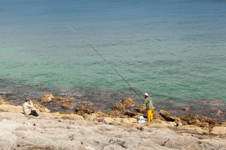 Tangier, Morocco - March 22, 2014: Arabic fisherman with a long rod stands on the coast of Atlantic ocean in Tangier, Morocco