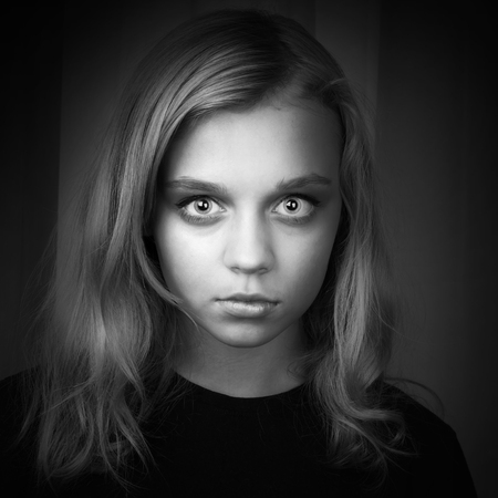 Serious blond Caucasian girl with mysterious hypnotic look photo