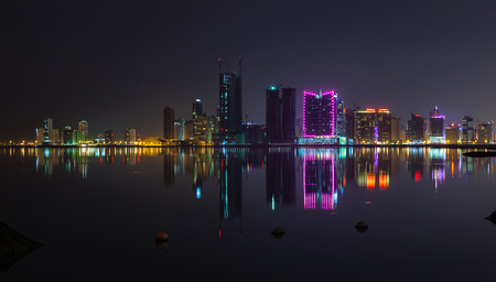 Night modern city skyline panorama with shining neon lights and reflection in the water. Manama, the Capital of Bahrain, Middle East photo