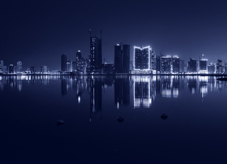 Night modern city skyline with shining lights and reflection in the water. Manama, the Capital of Bahrain, Middle East. Monochrome photo photo