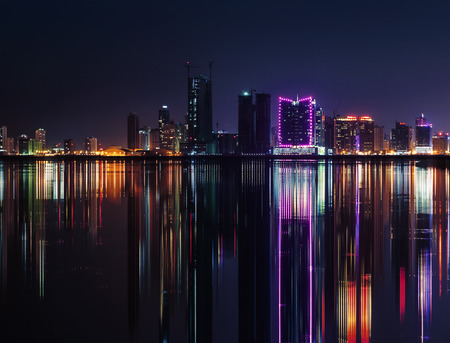Night modern city skyline with shining neon lights and reflection in the water. Manama, the Capital of Bahrain, Middle East photo