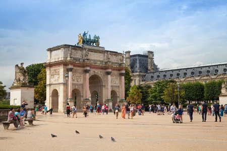 carrousel: Paris, France - August 7, 2014: Tourists walk near The Triumphal Arch (de Triomphe du Carrousel) in front of  the Louvre museum. Paris, France