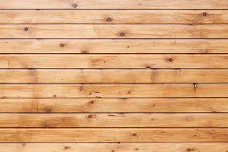 Background texture of natural uncolored wooden wall made of lining boards Imagens