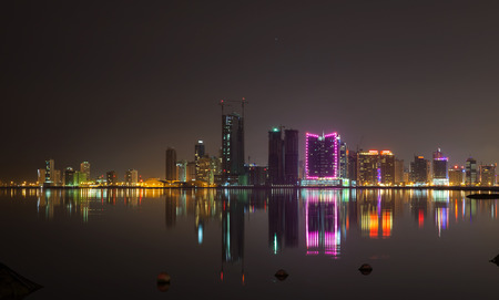 Night modern city skyline with shining lights and reflections in water. Manama, the Capital of Bahrain Kingdom, Middle East photo