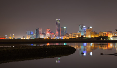 Night city skyline, shining lights and reflections in water. Manama, the Capital of Bahrain Kingdom, Middle East photo