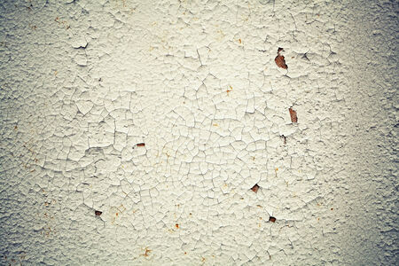 Rusted white metal wall with cracks on paint, background texture with vintage toned photo filter effect photo