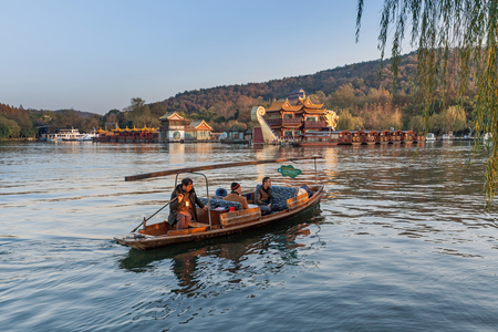 boatman: Hangzhou, China - December 5, 2014: Traditional Chinese wooden recreation boat with boatman floats on the West Lake. Famous park in Hangzhou city, China