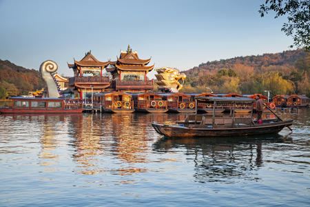 boatman: Hangzhou, China - December 5, 2014: Traditional Chinese wooden recreation boat with tourists and boatman floats on the West Lake. Famous park in Hangzhou city center, China Editorial