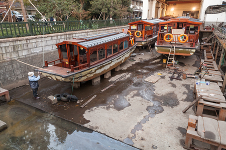 Hangzhou, China - December 5, 2014: Traditional Chinese wooden recreation boats under renovation in the shipyard. West Lake coast. Famous park in Hangzhou city, China