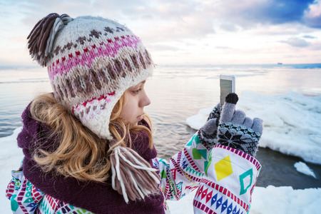 Little blond Caucasian girl taking pictures on her smartphone photo camera photo